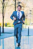 Urgent businessman runs in the city Royalty Free Stock Photo