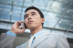 Urgent call. Businessman talking over the mobile phone in urban surroundings Stock Images