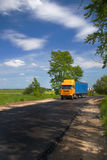 Urgent cargo delivery. Orange truck with cargo on the rural road Royalty Free Stock Photography