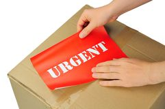 Urgent delivery. Hands placing label on parcel for urgent delivery Stock Image