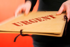 Urgent File. A woman bringing an urgent file. Red background and motion blur for stress and intensity of the situation. Focus at the rear of the urgent word royalty free stock photos