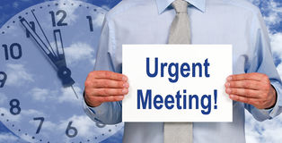 Urgent Meeting - Manager holding sign with text. Urgent Meeting - Manager holding sign with blue text, clock in the background royalty free stock photography