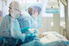 Urgent operation. Female surgeon performing operation with a nurse assisting her Stock Images