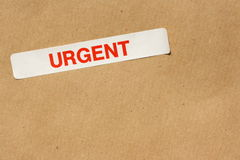 Urgent Sticker. Red Urgent sticker on a brown parcel paper background royalty free stock photos