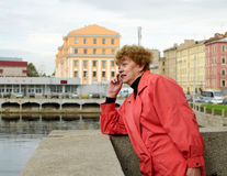 An urgent telephone call. Woman standing on a bridge makes a call to a friend Royalty Free Stock Photography