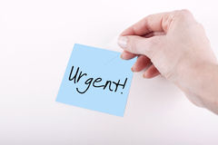 Urgent. Woman hand taping blue adhesive note paper with 'Urgent' word on white surface Royalty Free Stock Images