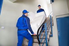Urheber, die Sofa On Steps tragen lizenzfreies stockfoto