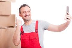 Urheberkerl, der Kasten zeigt und selfie und das Lächeln nimmt Lizenzfreies Stockbild
