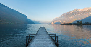 Uri lake. Wooden pier on the lake. Sunset in pastel colors. Mountains in the background royalty free stock image