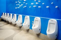 Urinal on blue wall Royalty Free Stock Photography