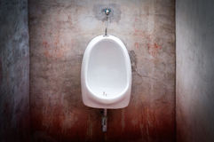 Urinal on old concrete red wall Royalty Free Stock Photo