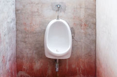 Urinal on old concrete red wall Stock Photos