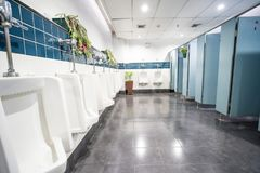 Urinal and toilet doors. Urinals and toilet doors in an old building for men only Stock Image