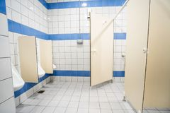 Urinal and toilet doors. Urinals and toilet doors in an old building for men only Stock Photos