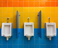 Urinals on colorful wall Royalty Free Stock Photo