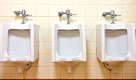 Urinals on dirty wall Royalty Free Stock Photography