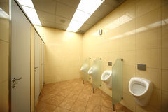 Urinals and doors in public restrooms Royalty Free Stock Photos