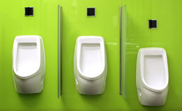 Urinals on green glass wall Royalty Free Stock Image