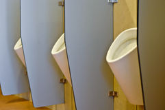 Urinals hinter Partitionen Stockbilder