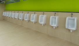 Urinals are lined up on the wall Stock Images