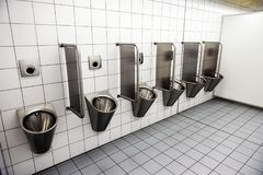 Urinals in men`s public modern toilet restroom sanitary or wc ar. Chitecture design concept Royalty Free Stock Images