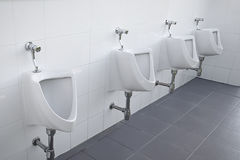 Urinals in public restroom Stock Photo