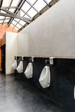 Urinals in public toilet Stock Photo