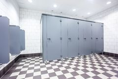Urinal and toilet doors. Urinals and toilet doors in an old building for men only Stock Photo