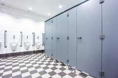 Urinal and toilet doors. Urinals and toilet doors in an old building for men only Royalty Free Stock Photography