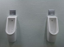 Urinals with two white painted a fly on the toilet Royalty Free Stock Images