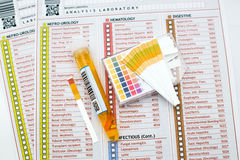 Urinalysis. Medical report and urine tube with reactive test strips Stock Photo