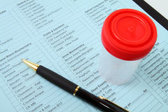 Urine test - medical checkup. Urine container and pen on lab test form stock photos