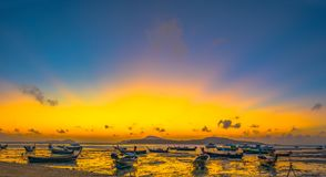 Uring sunrise above fishing boats. Yellow sky during sunrise above fishing boats in Rawai sea Phuket Thailand stock image