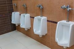 Urinoirs blancs de porcelaine dans la toilette publique Images libres de droits