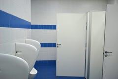 Urinoirs dans la salle du ` s d'hommes Photo stock
