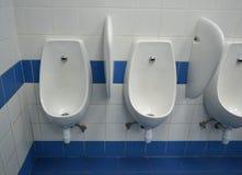 Urinoirs dans la salle du ` s d'hommes Images stock