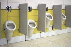 Urinoirs dans une toilette publique installée à de diverses tailles pour des personnes de ciel et terre Images stock