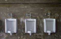 Urinoirs sur le mur en béton dans la toilette publique Photo libre de droits