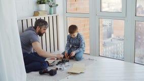 Urious mały syn i kochający ojciec jesteśmy ruchliwie z woodwork pracuje z instrumentami i jeżdżenie gwoździami z młotem zdjęcie wideo