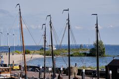Urk, The Netherlands - June 15 2020: Windmills on the coast with trees, boat masts and people. Wind power and Green energy. The