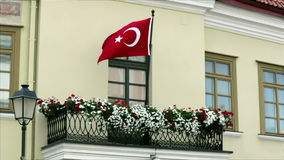 Turkish flag fluttering in the wind on a balcony with flowers.  stock footage