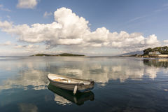 Urla Iskele, Izmir. Urla is populer holiday destination. I has beautiful nature. Cloudy reflection with a fishing boat is on the sea Stock Image