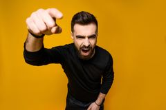 Urla sicure barbute dell'uomo che indicano dito fotografia stock