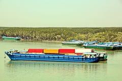 Urladdning av skytteln i porten av Saigon, Vietnam, Mekonget River Sikter av hytter, flodbanker och skepp, bogserbåtar fotografering för bildbyråer
