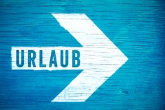Urlaub in German language, Holiday or Vacation text sign written on a white directional arrow on a blue wooden signboard. Concept for tropical beach vacation royalty free stock images