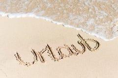 Urlaub scritto sulla sabbia dalla spuma dell'acqua Fotografia Stock Libera da Diritti