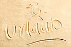 Urlaub-Text mit glänzender Sonne auf Strandsand Lizenzfreie Stockbilder