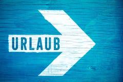 Urlaub w Niemieckiego języka, teksta znaku pisać na białej kierunkowej strzała na błękitnym drewnianym signboard, wakacje lub wak Obrazy Royalty Free