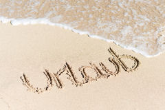 Urlaub Written On Sand By Water Surf. High angle view of word Urlaub written on sand by water surf Royalty Free Stock Photography