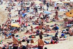 Urlauber, die auf dem Strand ein Sonnenbad nehmen Lizenzfreie Stockfotografie